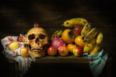 頭蓋骨、リンゴ、バナナ、ドラゴン フルーツ、柿、布や木製のテーブルにキャンドルのある静物 写真素材