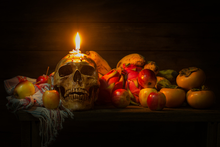 頭蓋骨、リンゴ、バナナ、ドラゴン フルーツ、柿、布や木製のテーブルにキャンドルのある静物 写真素材 - 88024230