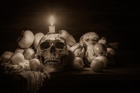 頭蓋骨、リンゴ、バナナ、ドラゴン フルーツ、柿、布や木製のテーブルにキャンドルのある静物 写真素材 - 88125637