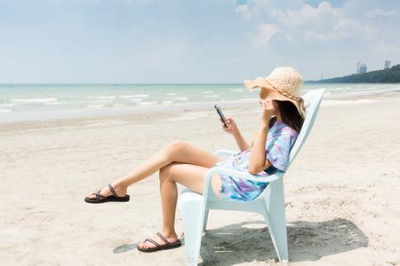 帽子の女はビーチでのデッキチェアで日光浴でおくつろぎください。旅行、休暇、概念。 写真素材 - 88993179