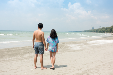 Young couple in love, playing together on the beach