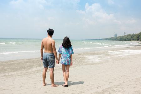 恋に若いカップル、ビーチで一緒に遊んで