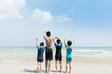 4人の子供がビーチに座っている。