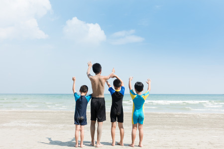 Four kids sitting on the beach.