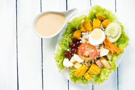 Fresh healthy salad on white wooden table. View from above with copy space