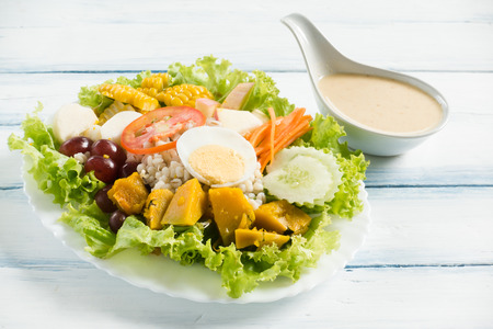 Fresh salad on white plate on wooden table