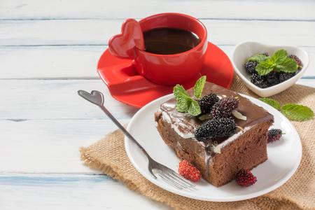 チョコレート ナッツのブラウニー ケーキ果実で飾られて、ミントの葉。一杯のコーヒー、白いテーブルに荒布を着た。選択と集中