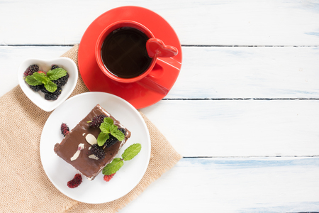 chocolate nut brownie cake decorated with berries and mint leaves. Cup of coffee, sackcloth on white table. selective focus 写真素材