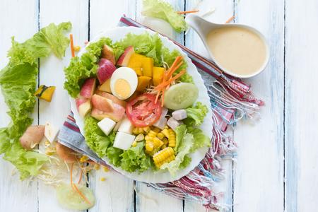 木製のテーブルの上に白いプレートに新鮮な果物や野菜のサラダ 写真素材 - 89610994