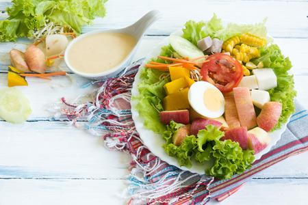 木製のテーブルの上に白いプレートに新鮮な果物や野菜のサラダ