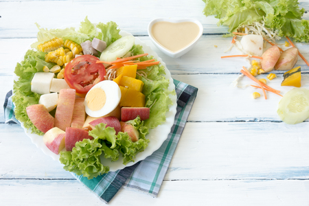 Fresh Fruit and vegetable salad on white plate on wooden table