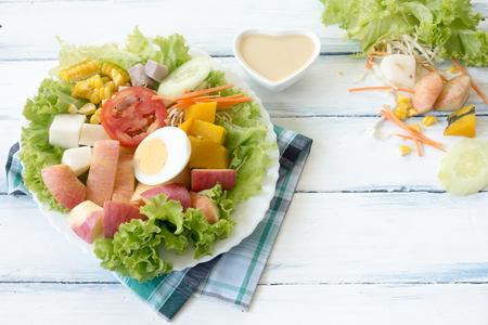 新鮮なフルーツ、木製テーブルの上の白い皿に野菜サラダ