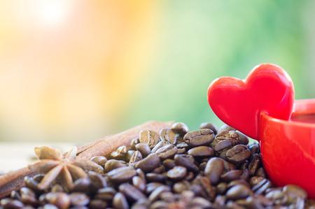 コーヒー豆のクローズアップ, 手に持っていた心の形で赤いカップ, 自然の背景にスターアニスとシナモン, 選択的焦点.