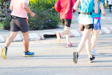 Group of Marathon running race, people feet on city road, Motion blur Flower background, Selective focus 写真素材