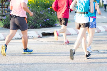 マラソンランニングレースのグループ、都市道路の人々の足、モーションブラー花の背景、選択的な焦点 写真素材