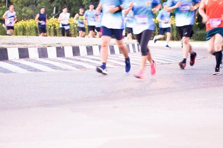 マラソン レースを実行する、都市道路、モーション ブラーの花背景、選択と集中で人々 の足のグループ