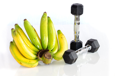 Fitness dumbbells with banana isolated on white background Imagens - 102630229