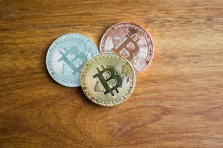 golden bitcoin, silver bitcoin, bronze bitcoin on wooden