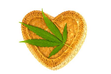 Marijuana leaves, cannabis on heart shape Bamboo basket, white background Stock fotó