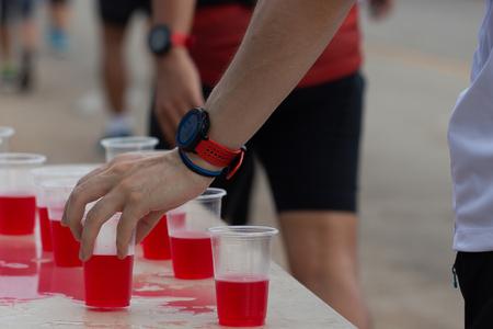 Marathon runner picking up mineral salt water at service point Imagens - 102960829