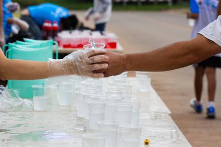 Marathon runner picking up mineral salt water at service point