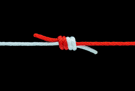 Tie the knot with red and white rope on black background Imagens