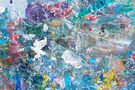 close up the colorful water color art and abstract on top of a child table covered in paint splatter