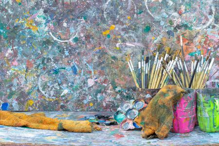 paintbrush and colorful artist palette on dirty paints background