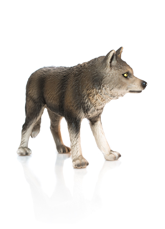 Young wolf toy. Isolated young spotty wolf toy standing on white background profile view.