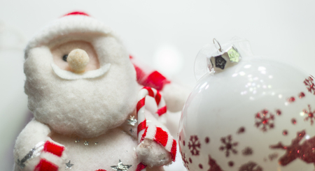 plushie: Cute stuffed toy Santa Claus giving a Christmas present. Stuffed toy Santa Claus, a bag of presents and Christmas tree