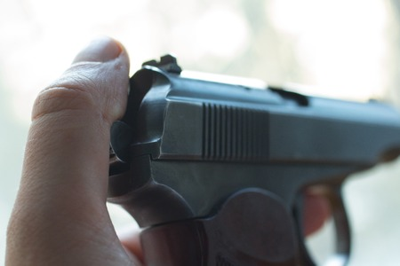 finger on trigger: gun in a human hand on a background of old boards