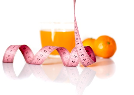 symbolize: orange fruits and measuring tape on a white background to symbolize a healthy diet