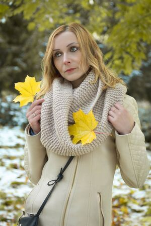 very beautiful girl posing in beige coat and a scarf in autumn park and holding maple leaves Stock Photo