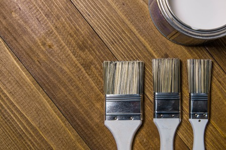 Painting brushes near a metal jar with white paint on a wooden table Stock Photo