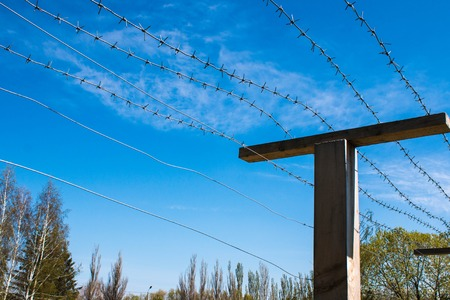 Poles with barbed wire at the state border Stock Photo