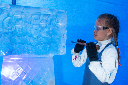Girl of seven years in the master class on ice sculpture Stock Photo