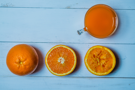 A glass of fresh orange juice with sliced oranges on a wooden table. The preparation of fresh orange juice is primordial to product advertising Imagens