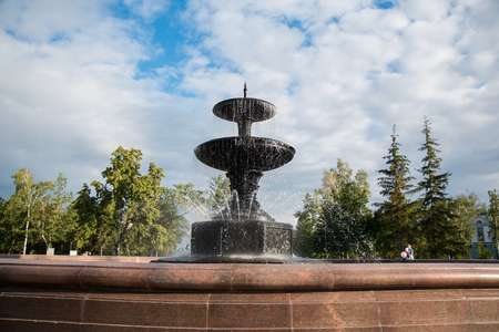 water feature: Large granite fountain in a city park on a background of a bright blue sky