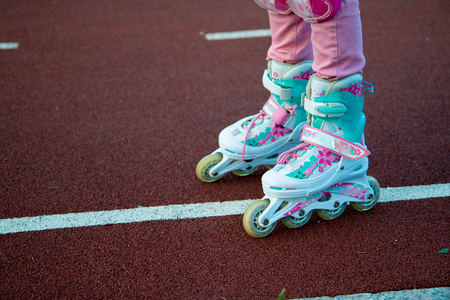 roller: A fragment of childrens legs in roller skates on a bicycle path