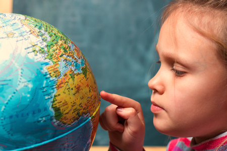 girl - a child of seven years on the geography lesson near  globe  the world against the background  the school board