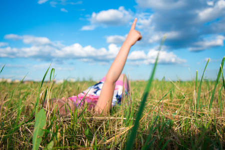 clovers: Happy dreamy girl lies in the park on grass and shows on clouds, dreams