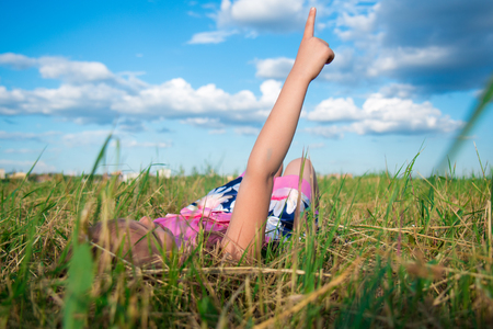 Happy dreamy girl lies in the park on grass and shows on clouds, dreams