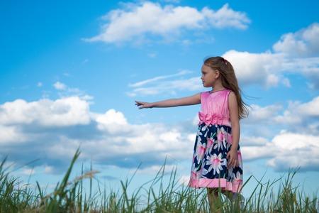 Portrait d'une fille de sept ans avec une robe rose vif sur l'herbe dans le parc