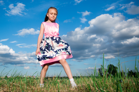 Portrait of a seven year old girl in a bright pink dress on the grass in the park Stock Photo