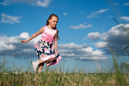 Portrait of a seven-year-old girl in a bright pink dress who jumps and plays on the grass in the park on a sky background Stock Photo
