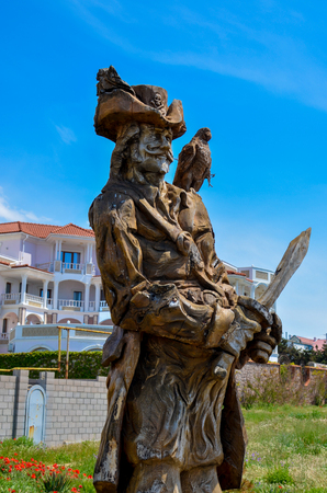 A wooden figure of a pirate with a parrot on the Black Sea coast in the suburbs of Sevastopol, the Republic of Crimea. 2017 year