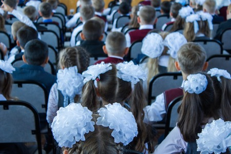 many children sit dressed in the assembly hall at a concert dedicated to the Day of Knowledge Day on September 1. the picture is taken from the back