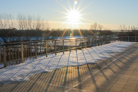 The sun at sunset on the pier frozen Siberian river. Texture of snow and metal fence