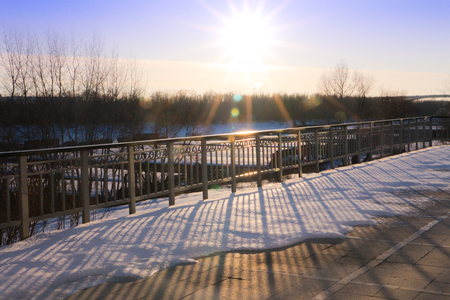 the sun at sunset on the pier frozen Siberian river. texture of snow and metal fence Imagens