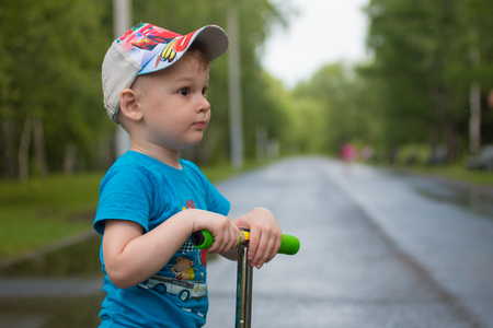 a little boy in a cap on his green scooter riding in a pack Imagens